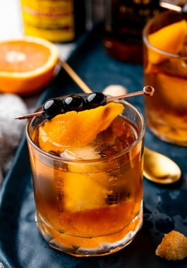 Old fashioned cocktail garnished with cherries and an orange twist.