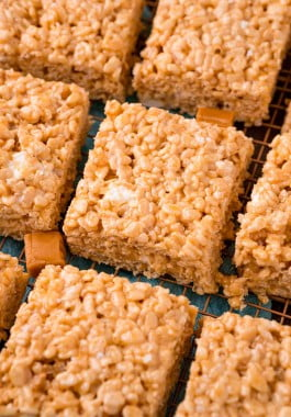 Squares of salted caramel Rice Krispies treats on a wire cooling rack.