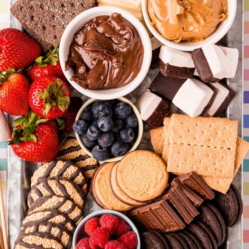 Decked out s'mores charcuterie board with graham crackers, chocolate, marshmallows, fruit, and cookies.