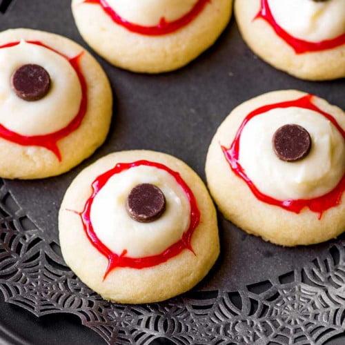 Prepared eyeball cookies on a black plate.