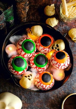 Black bowl filled with Halloween hot chocolate bombs, decorated with spider webs, lights, and skulls.