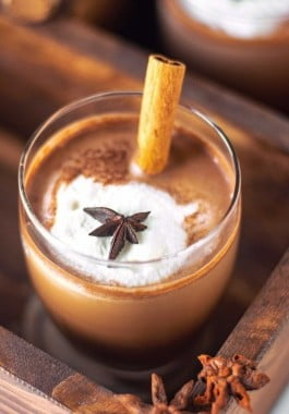 Top down view of prepared spiced hot chocolate garnished with whipped cream, star anise, and a cinnamon stick.